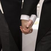 Same-sex male couple wearing tuxedos holding hands.