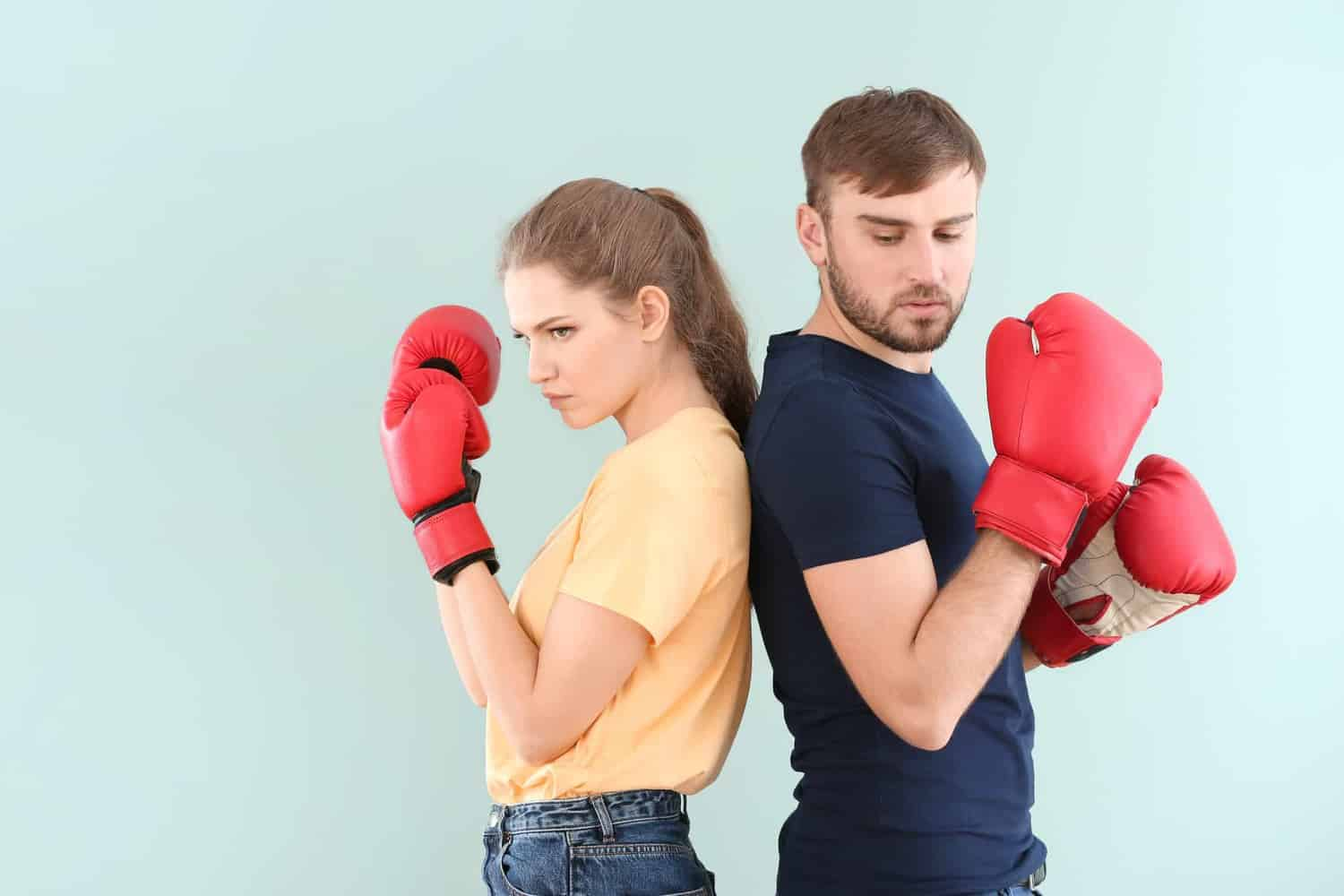 A man and a woman wearing boxing gloves, ready to fight.
