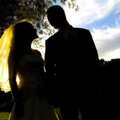 Bride and groom at an outdoor wedding with blue sky.