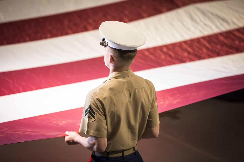 U.S. Marine holds a large American flag.