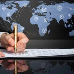 Map of world with businessman signing document.