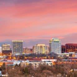 Colorado Springs city skyline & mountains at sunset.