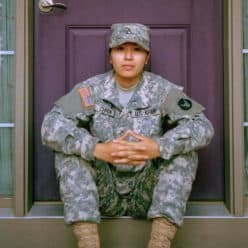 Female U.S. Army soldier sitting on front doorstep.