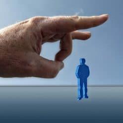Large hand flicking away a man
