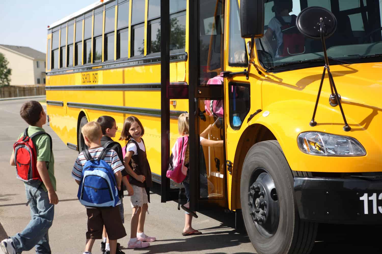 ;Young elementary school kids boarding a yellow school bus.