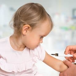 Doctor giving vaccine to little girl.