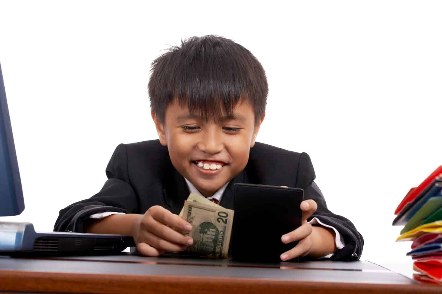 Boy sitting at desk removing cash from a wallet.