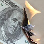 Burning a hundred dollar bill.
