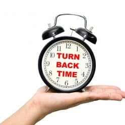 """Hand holding clock saying """"turn back time."""""""